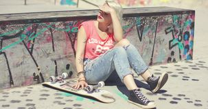 Young woman waiting at a skate park for a friend stock video footage