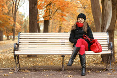 A young woman waiting for someone on a bench. A young brunette Caucasian woman in warm clothes waiting for someone on a bench. The image is taken on an Autumn royalty free stock image