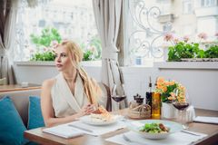 Young woman waiting someone who late, and looking for her boyfriend in coffee shop. Portrait of young unhappy stressed beautiful f. Emale sitting in modern urban Stock Photo