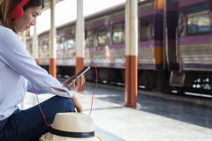 Young woman waiting on the station platform with backpack on tra Stock Photos
