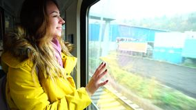 Young woman waiting for  train approaching  city to stop at  station in  autumn afternoon. Portrait of elegant female that looks at  autumn cityscape through stock video
