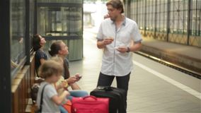 Young woman waiting for the train and holding a coffee cup while waiting on a bench at a railway station, family eatting. And waiting, traveling stock footage