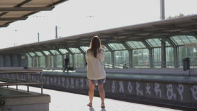 Young woman waiting for a train at platform at the stock video