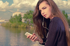 Young woman waiting your call. Dressing in a black wear,  a young caucasian lady is standing by river, holding a mobile Royalty Free Stock Image