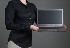 Young woman or waitress showing laptop screen. Business woman presenting a software or showing an application. Girl holding laptop with dynamic pose and black Stock Photography