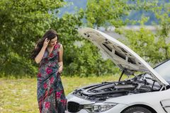 Young woman waits for assistance near her car broken down on the. Road side Royalty Free Stock Photos