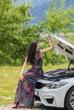 Young woman waits for assistance near her car broken down on the. Road side Stock Image