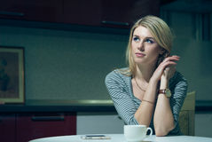 Young woman waits by the phone on a night kitchen Stock Photography
