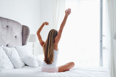 Young woman after wake up in the bedroom. Beautiful woman stretching in her bed after wake up in the bedroom stock images