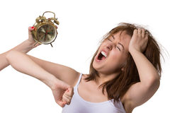 Young woman wakes up from alarm clock and yawns in the morning. Royalty Free Stock Images