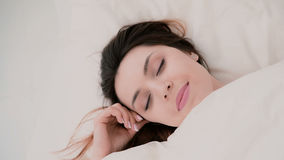Young woman wakes up and have fun in bed. Girl start to hiding under sheets, making funny face and blowing hair Royalty Free Stock Photos