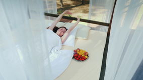 A young woman wakes up on a lounger, covered with curtains, near her a plate of fruit. Gorgeous romantic holiday stock video footage