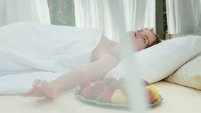 A young woman wakes up on a lounger, covered with curtains, near her a plate of fruit. Gorgeous romantic holiday stock video