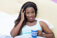 Young woman wakes up in music and good humor Royalty Free Stock Image