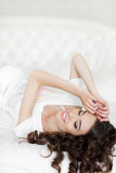 Young woman wakes up in a white bed in the morning. Young beautiful woman brunette with long curly hair, in a white night shirt, wakes up in the morning on a royalty free stock image
