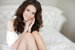 Young woman wakes up in a white bed in the morning. Young beautiful woman brunette with long curly hair, in a white night shirt, wakes up in the morning on a stock photo