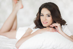 Young woman wakes up in a white bed in the morning Stock Photo