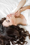 Young woman wakes up in a white bed in the morning Royalty Free Stock Images