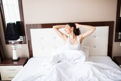 Young woman waking up stretching in bed at home Royalty Free Stock Photos