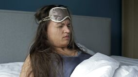 Young woman waking up suffering headache and hangover after drinking alcohol.