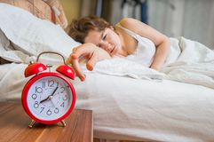 Young woman is waking up and turning off her alarm clock Stock Photography