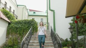 Young woman walk down on stairs. stock footage