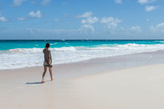 Young woman walk on an empty wild beach Stock Images