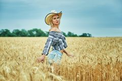 A young woman on a walk in the field with wheat Royalty Free Stock Photo