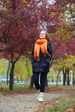 Young woman walk on footpath in autumn park, yellow leaves and trees royalty free stock photos