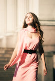 Young woman walking. Young woman in pink dress walking. Soft colors Stock Photo