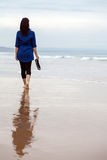 Young woman walking alone on a beach Stock Photography