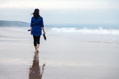 Young woman walking alone on a beach Stock Image