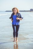 Young woman walking alone on the beach Stock Photography