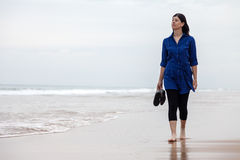 Young woman walking alone in a deserted beach Stock Photo