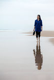 Young woman walking alone in a deserted beach Stock Photos
