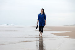 Young woman walking alone in a deserted beach Royalty Free Stock Image