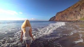 Woman walking along the beach stock video footage