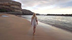 Woman walking along the beach. Young woman walking along the beach stock footage