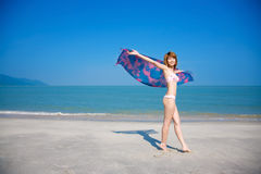 Young woman walking along the beach. Young woman in bikini holding floral scarf walking along the beach Royalty Free Stock Image