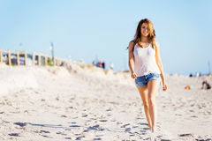 Young woman walking along the beach Stock Photography