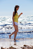 Young woman walking along the beach Stock Images
