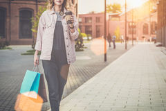 Young woman in glasses is walking along city street,carrying shopping bags and holding cup of coffee. Stock Photo