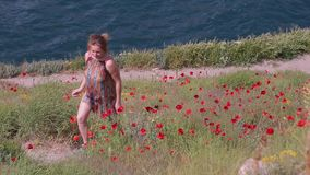 A young woman is walking along a poppy field. Sunny day stock video