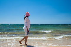Young woman  walking along the seashore Stock Images
