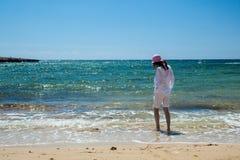 Young woman walking along the seashore Royalty Free Stock Images