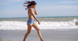 Young woman walking along the surf stock video