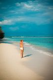 Young woman walking along tropical beach Stock Photography