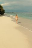 Young woman walking along tropical beach Royalty Free Stock Image