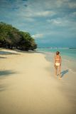Young woman walking along tropical beach Stock Images