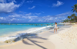 Young woman walking along white sand tropical beach. Royalty Free Stock Photo